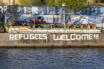 Refugees welcome graffiti and refugee boat in Berlin