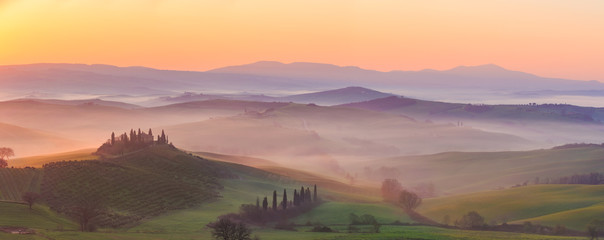 Misty sunrise in the Val d'Orcia, or Valdorcia, a region of Tuscany, central Italy, which extends from the hills south of Siena to Monte Amiata.  Fototapete