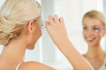 woman fixing makeup with cotton swab at bathroom