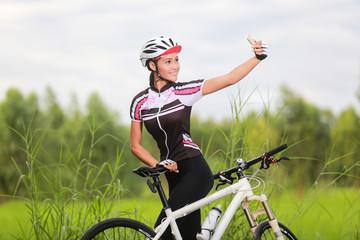 Beautiful woman cyclist take a self portrait with smart phone