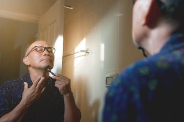 Asian old man is shaving his beard in the bathroom.