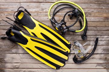 Mask, fins, snorkel and regulator on wooden desk
