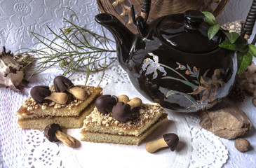 Pieces of cake with chocolate mushrooms and teapot on white openwork napkin