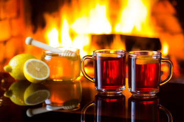 Two cups of hot drink with fireplace on background