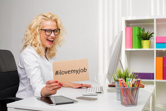 "Woman in office showing ""I love my job"" cardboard"