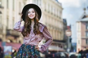 Outdoor portrait of a young beautiful fashionable happy lady posing on a street of the old city. Model wearing stylish clothes. Girl looking at camera. Female fashion. City lifestyle. Copy space