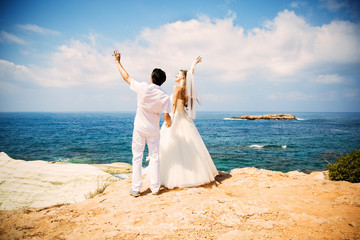 Elegant bride and groom walking on the beach, wedding ceremony, Mediterranean Sea.