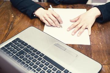donna in ufficio con contratto di lavoro e notebook