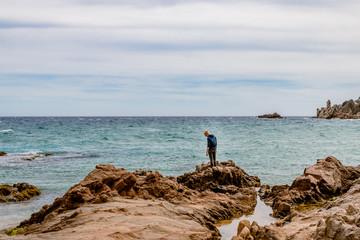 Jeune homme sur les rochers dans une Crique à Blanes