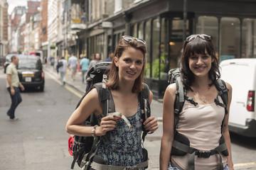 Candid portrait of two women backpackers on street, London, UK