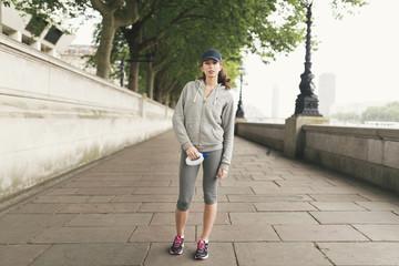 Full length portrait of female runner holding water bottle