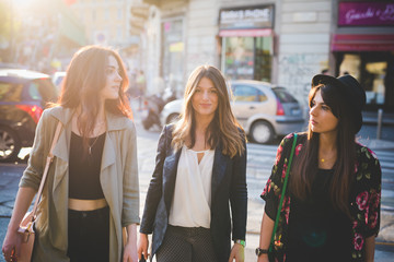 Three young women strolling on city street