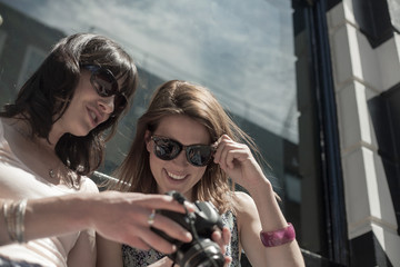 Two women wearing sunglasses reviewing  camera photographs on city street