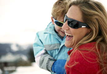 Skiing mother carrying toddler son