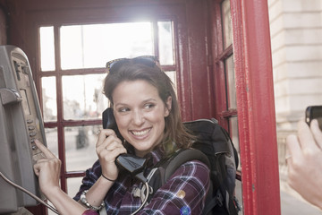 Two women backpackers taking smartphone photograph in red telephone box, London, UK