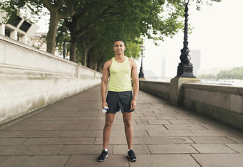 Full length portrait of male runner holding water bottle