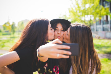 Three young female friends cheek kissing for smartphone selfie in park