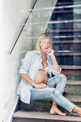 Portrait of full term pregnancy young woman sitting on stairway