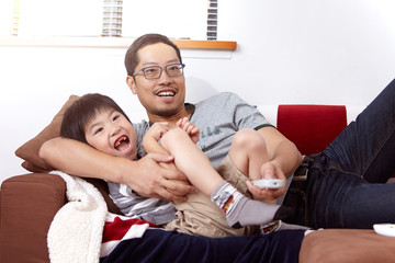 Young, modern Chinese family of father and young son sitting on sofa watching television together at home