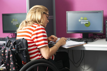 Teenage girl in wheelchair writing up file notes in class