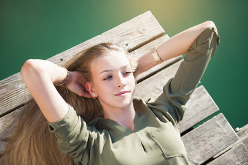 Overhead view of young woman lying on wooden decking, hands behind head looking away