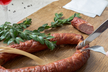 Cutting smoked sausage ring in rustic style