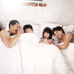Young Chinese family of parents and two young children laying in bed together at home