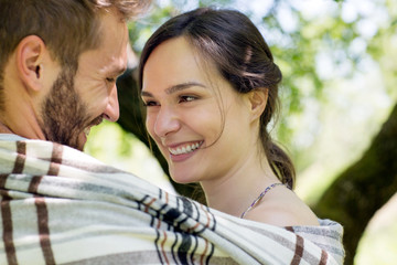 Head and shoulders of young couple wrapped in blanket face to face smiling