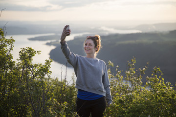 Woman taking selfie on hill, Angel's Rest, Columbia River Gorge, Oregon, USA
