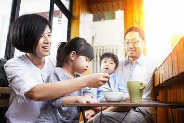 Young Chinese family having breakfast on the balcony in the sunshine together