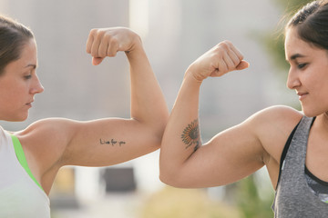 Two friends comparing bicep muscles