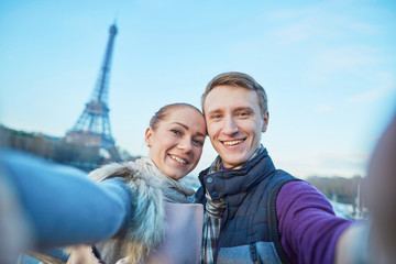 Happy couple of tourists taking selfie near the Eiffel tower in Paris