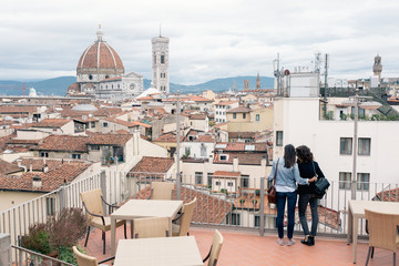 Rear view of lesbian couple standing of roof terrace looking at view of Giotto's Campanile and Florence Cathedral, Tuscany, Italy