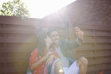 Mid adult couple taking smartphone selfie at rooftop party