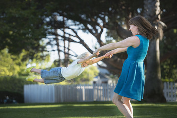 Mother swinging son around, outdoors