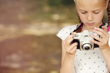 Cropped view of girl holding film camera looking down
