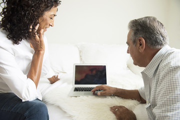 Mature woman and husband looking at laptop on bed