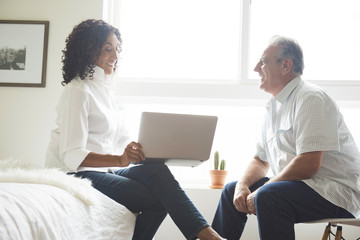 Mature senior couple using laptop in bedroom