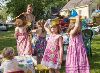 Group of children at kindergarten graduation, wearing paper mortar boards