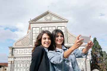 Lesbian couple using smartphone to take selfie in front of church, Piazza Santa Maria Novella, Florence, Tuscany, Italy