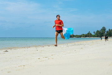 The man trains running on the beach with a parachute