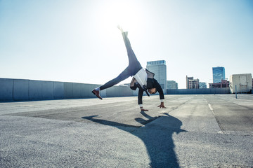 Businessman doing handstand on roof terrace, Los Angeles, California, USA
