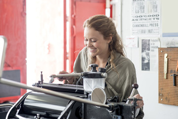 Female letterpress printer preparing printing machine in workshop