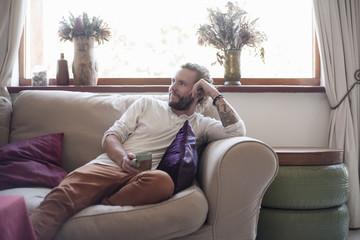 Mid adult man relaxing on sofa, drinking tea