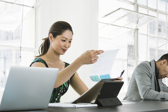 Businesswoman smiling over letter at office