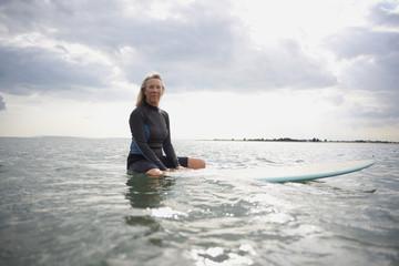 Portrait of  senior woman sitting on surfboard in sea