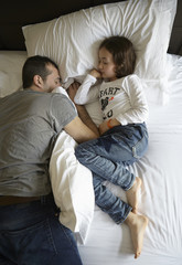 Overhead view of father and daughter sleeping on bed