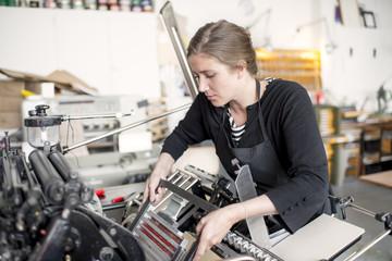 Female letterpress printer preparing print machine in workshop