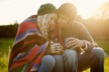 Romantic young couple wrapped in blanket with tea drinks