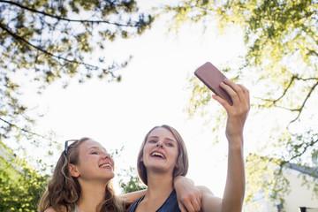 Two teenage girls in park taking smartphone selfie